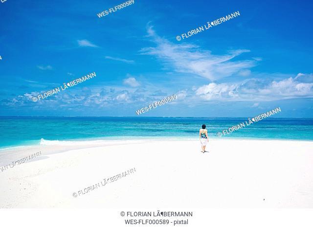Maledives, Ari Atoll, young woman walking at dream beach