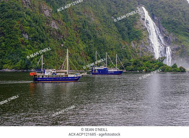 Cruise boats near a waterfall in Fiordland National Park, South Island, New Zealand