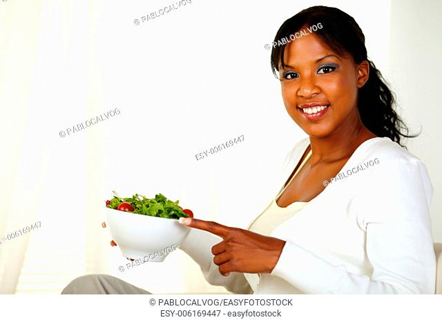 Portrait of a young woman smiling at you while pointing healthy vegetable salad on a bowl at home indoor. With copyspace
