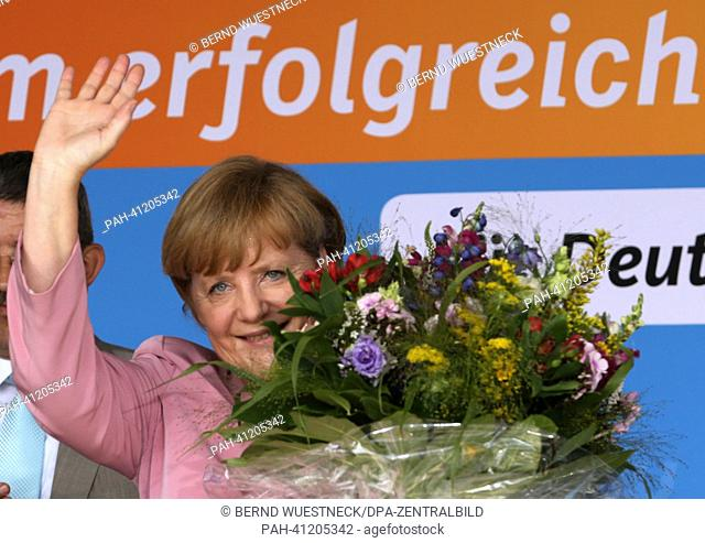 German Chancellor Angela Merkel (CDU) waves and holds a bouquet of flowers at the start of an election campaign event in Zingst, Germany, 22 July 2013