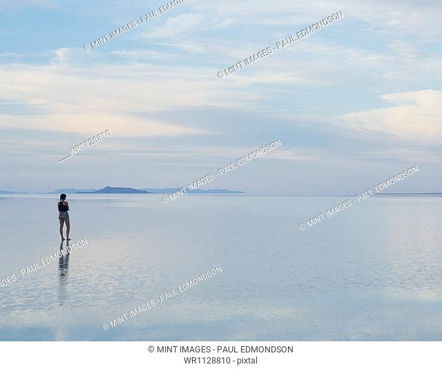 A woman standing on the flooded Bonneville Salt Flats at dusk. Reflections in the shallow water