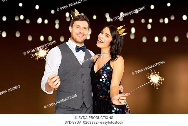 happy couple with crowns and sparklers at party