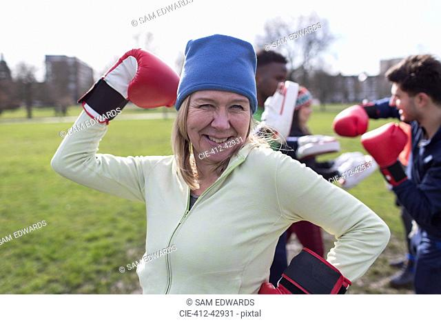 Portrait smiling, confident senior woman boxing in park