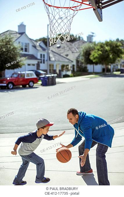 Father and son playing basketball in driveway