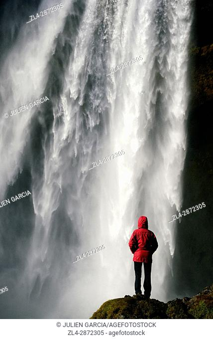 Iceland, Sudurland region, woman in front of Skogafoss waterfall, Model Released