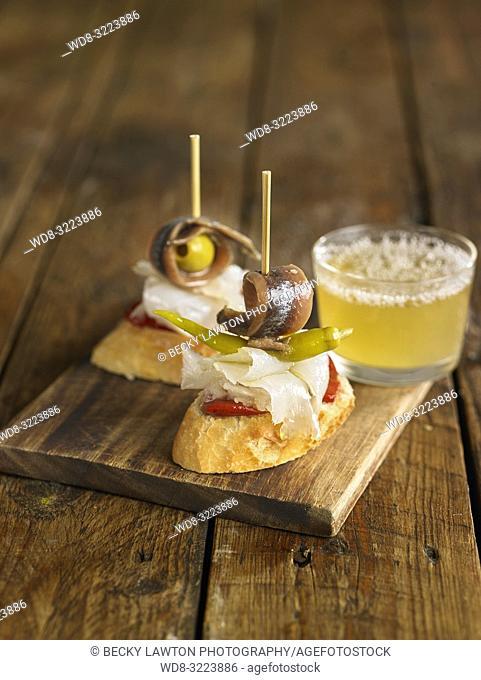 tapas de anchoas y pimientos con vaso de cerveza / Anchovies and peppers with beer glass