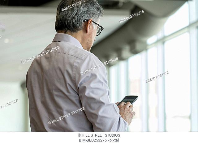 Hispanic businessman texting on cell phone