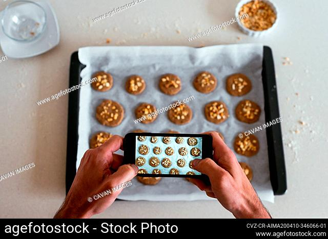 Overhead view of a young man taking a photo of his home-made cookies