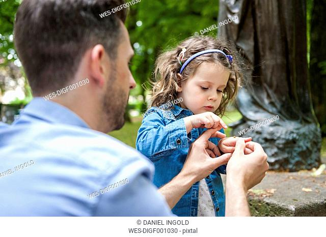 Father and daughter examining ladybird on hand