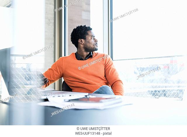 Casual businessman sitting at desk looking out of window