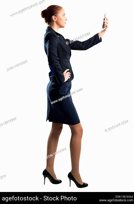 Young beautiful woman taking selfie photo with smartphone. Confident and stylish businesswoman in dark blue suit. Corporate businessperson isolated on white...