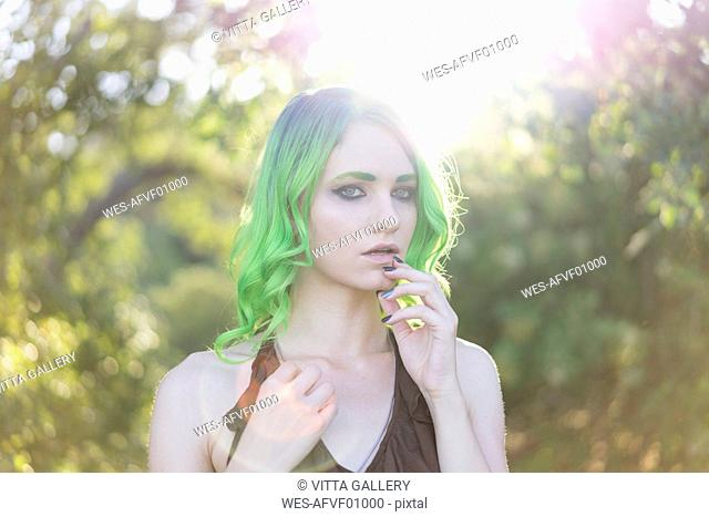 Portrait of young woman with dyed green hair and eyebrows at backlight