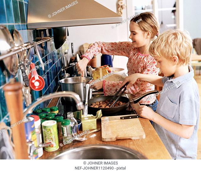 Boy and girl preparing food in kitchen