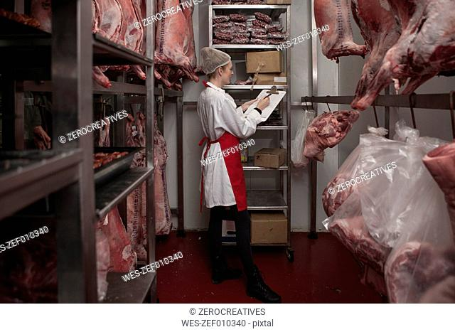 Woman with clipboard in butchery cold store