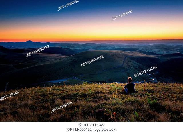HIKERS CONTEMPLATING THE FIRST LIGHT OF DAY OVER THE PUY DE DOME AND THE PUYS MOUNTAIN RANGE SEEN FROM THE PUY DE LA TACHE, SANCY MOUNTAINS, MONT-DORE