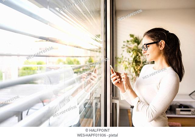Smiling woman standing at window at home using smartphone