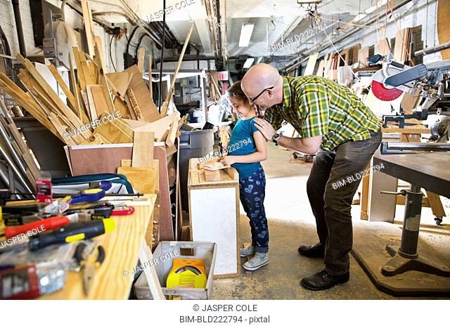 Father and daughter woodworking in workshop