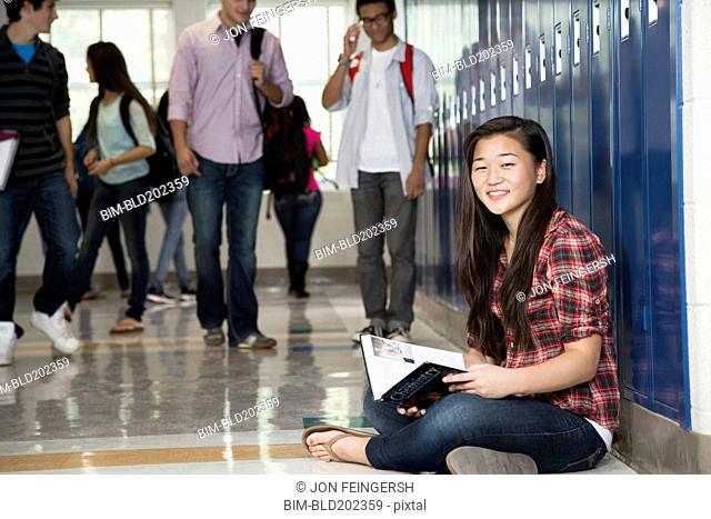 Asian student sitting in high school corridor