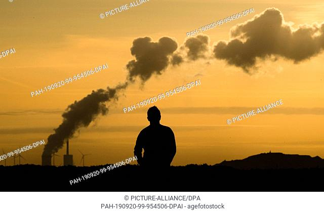 20 September 2019, Lower Saxony, Hanover: A jogger pauses at Kronsberg shortly after sunrise, while steam rises on the horizon from the Mehrum coal-fired power...