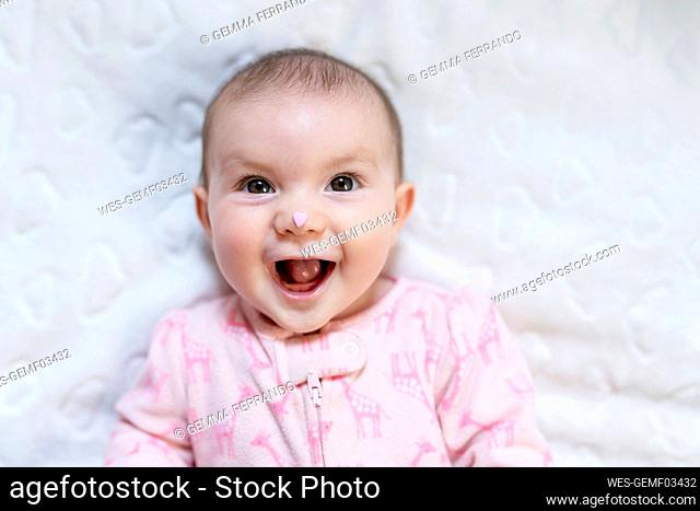 Portrait of happy baby girl with pink heart-shaped candy on nose