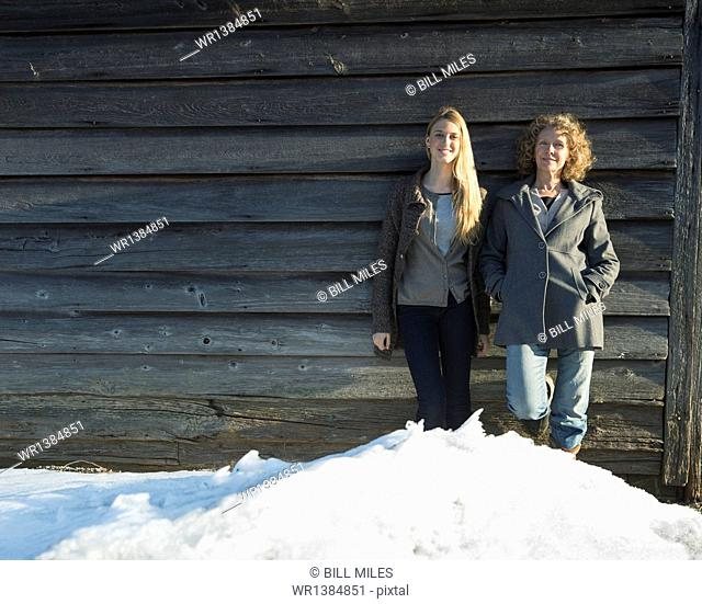 A mother and daughter standing leaning against the wooden wall of a barn on a farm. Snow piled up at their feet