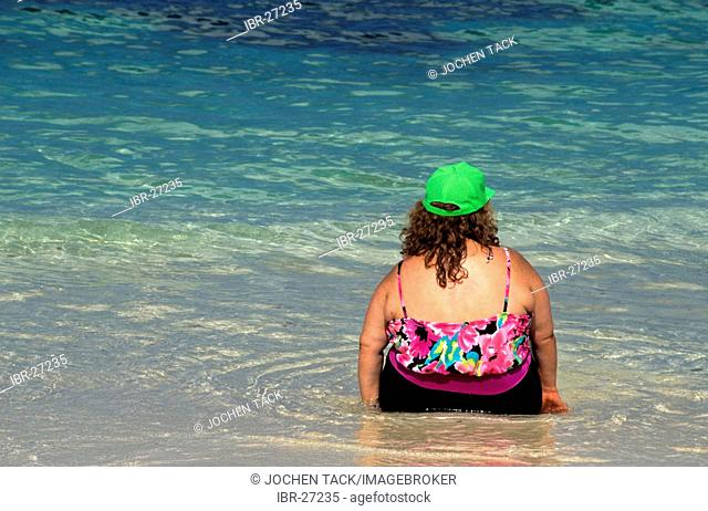 BHS, Bahamas, New Providence, Nassau: Fat woman on the beach. Independent state in the West Indies, member of Comonwealth of Nations