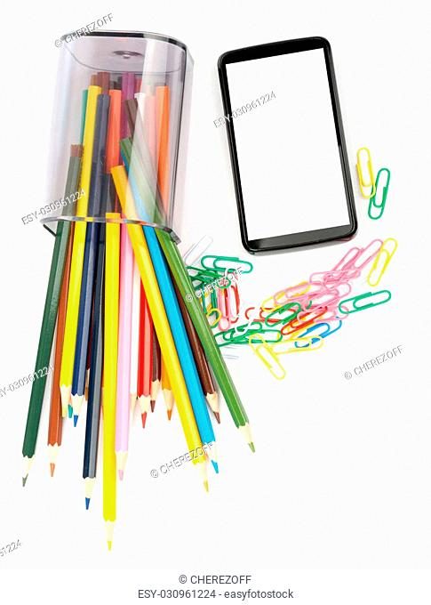 Fallen pencil cup with crayons and smartphone on isolated white background