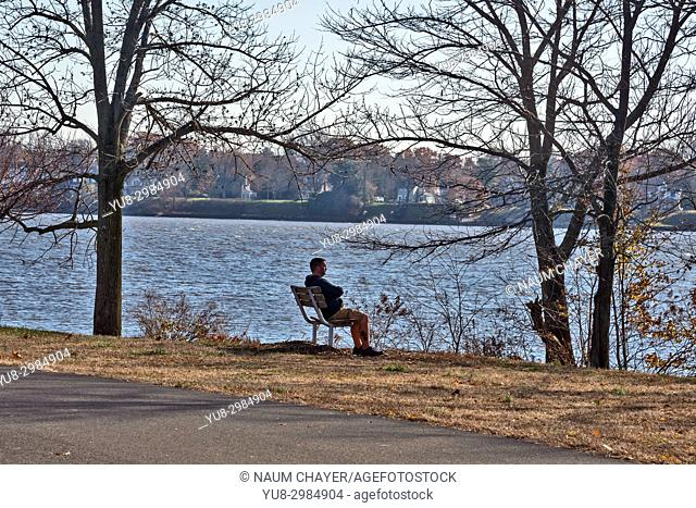 A young man is resting on a bench in an autumn park, Neshaminy State Park, Bucks County, Pennsylvania, USA