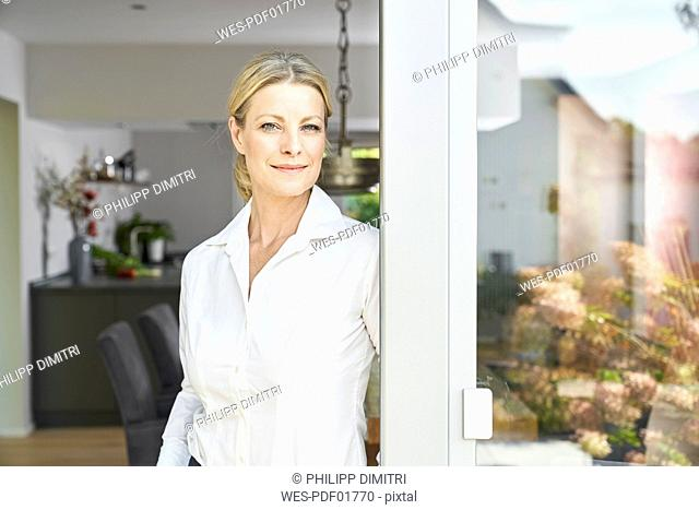 Portrait of confident woman standing at French door at home