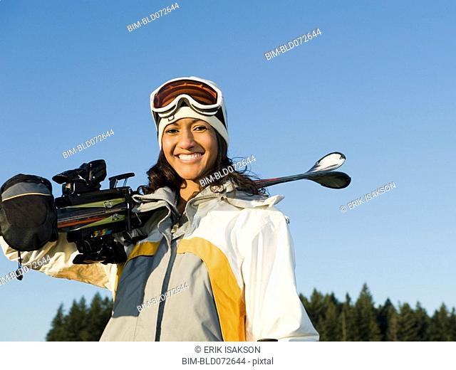 Mixed race woman holding skis