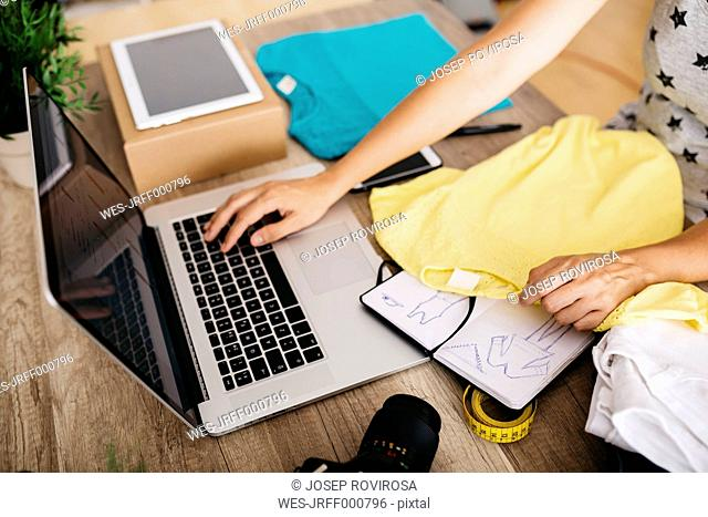 Woman with garment using laptop on desk