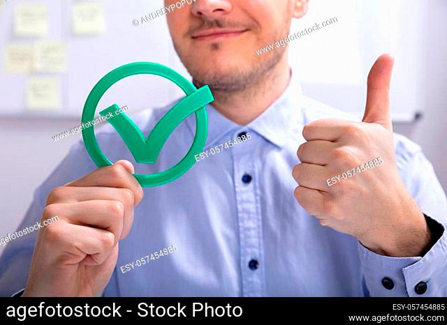 Smiling Young Businessman Showing Thumbs Up Sign With Green Check Mark Icon