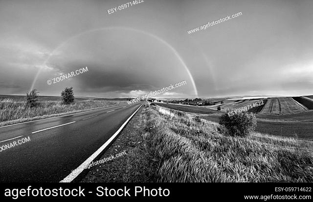 Grayscale. Spring rapeseed and small farmlands fields after rain evening view, cloudy pre sunset sky with rainbow and rural hills