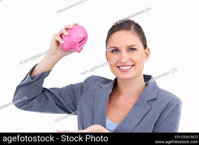 Smiling bank clerk with piggy bank in her hand