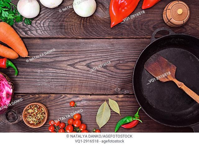 Black frying pan and fresh vegetables on a brown wooden background, empty space in the middle