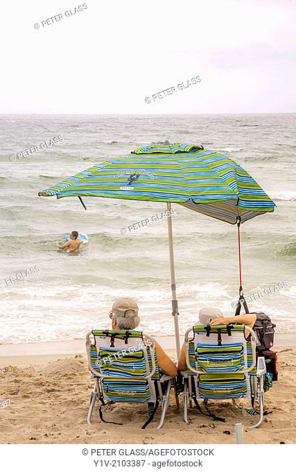 Older couple sitting under an umbrella at the beach