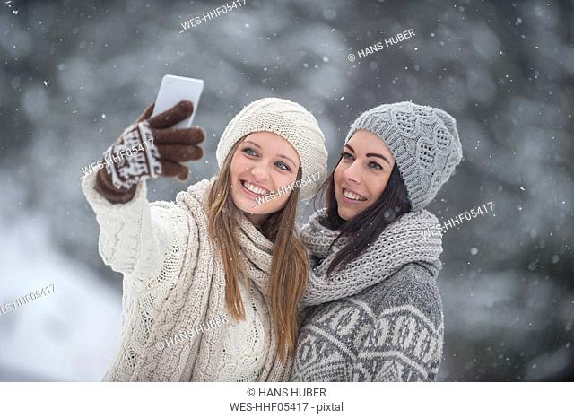 Two young women taking a selfie in snowfall
