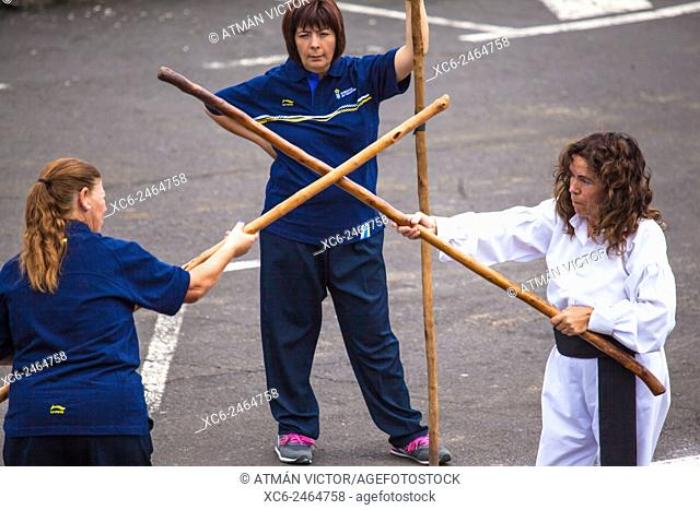 Women playing the canarian stick fight in a public exhibition in the open air