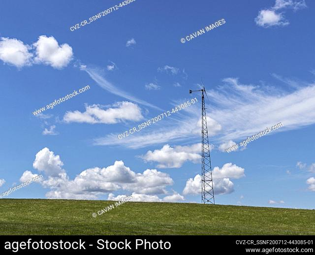 Windmill in green field with bright blue sky on summer day in Maine