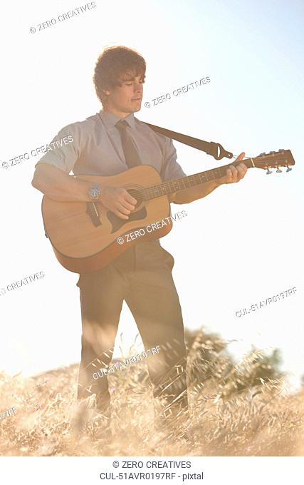 Man playing guitar in tall grass