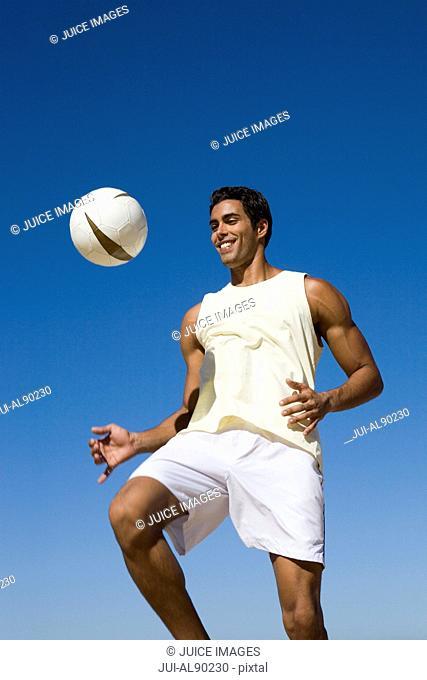 Man bouncing ball on knee