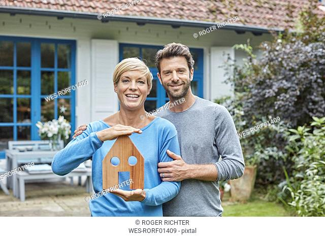 Portrait of smiling couple standing in front of their home holding house model