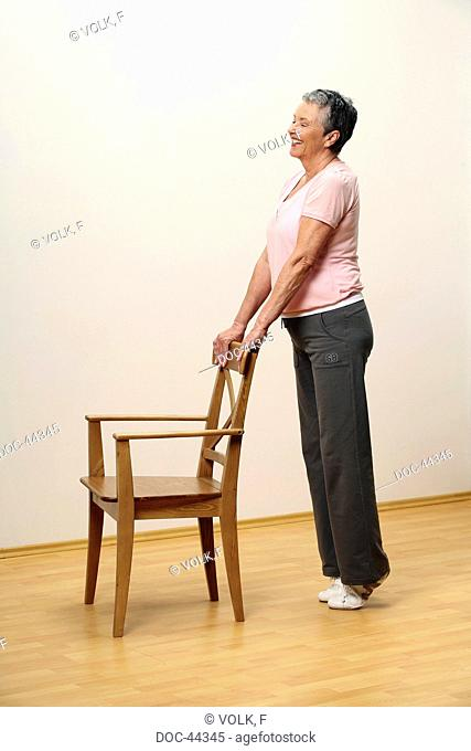 older woman doing gymnastics with a chair - woman is standing on tiptoe - pumping - muscularity - senior