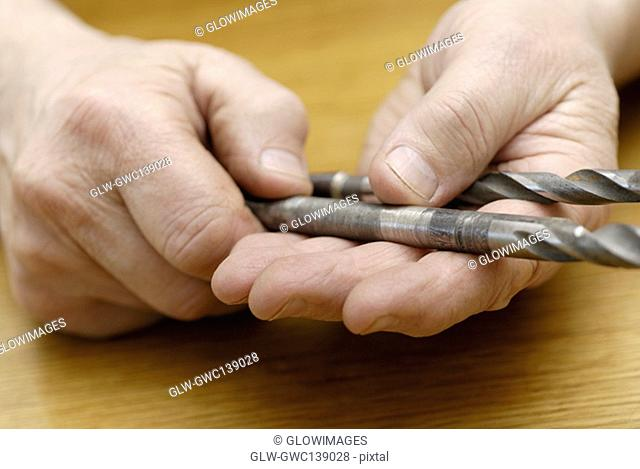 Close-up of a person's hand holding drill bits