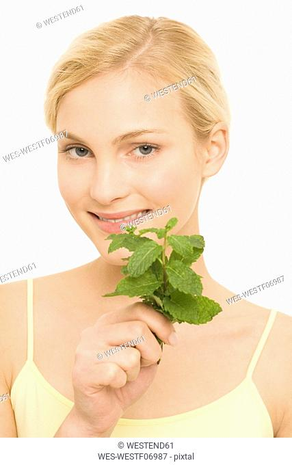 Young woman holding sprig of mint, portrait
