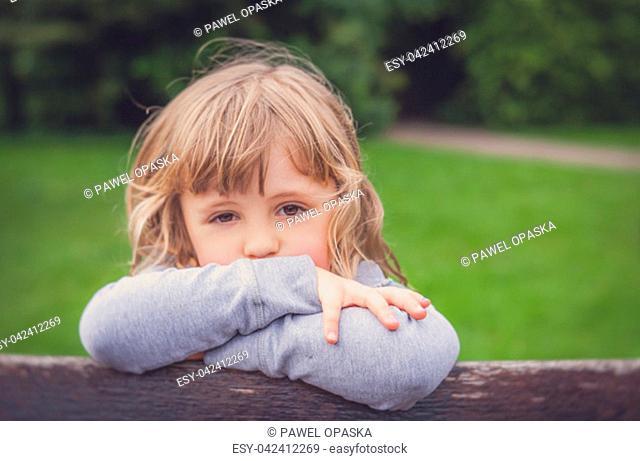 Portrait of a little sad Caucasian girl in a garden in summer