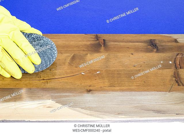 Woman's hand treating plank with steel wool and vinegar