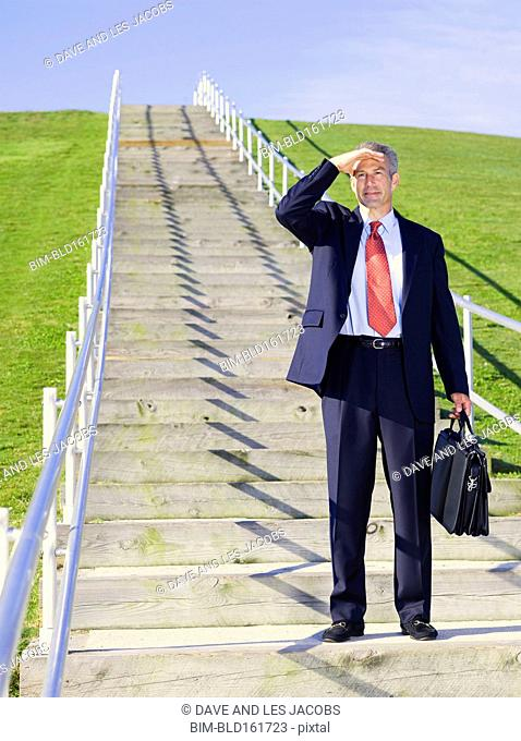Curious Caucasian businessman standing on outdoor staircase