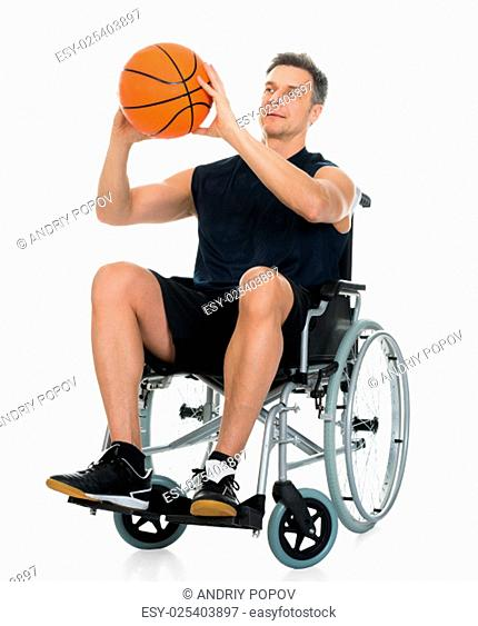 Handicapped Man On A Wheelchair Working Out With Dumbbell Over Black Background