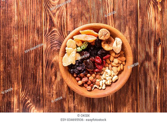 Dry fruits and nuts in bowl on wooden table. Copy space background - close up healthy sweets
